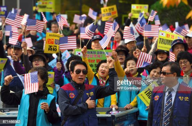 ProTrump supporters wave the US flags near the National Assembly in Seoul on November 8 2017 as US President Donald Trump is due to address the South...
