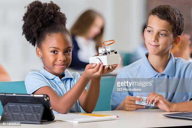 Proud African American schoolgirl holds up robot