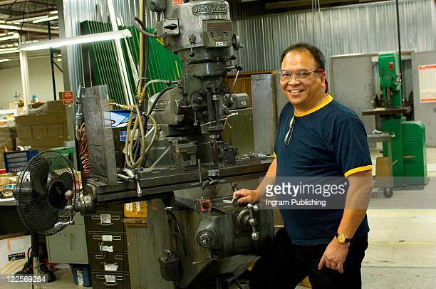 Proud Asian worker standing in front of drill press.
