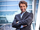 Proud Italian Businessman smiling in front of his office. He is a successful man with a lot of leadership.