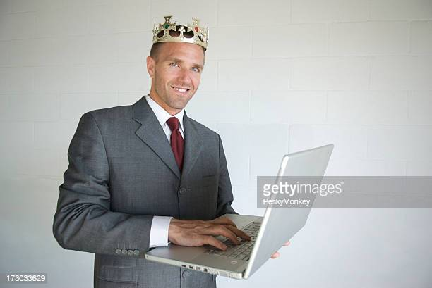 Proud Businessman Wearing Crown Smiling with Laptop