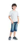 Smiling little boy with freckles standing isolated on white background. Portrait of satisfied cute child in casual clothes looking at camera. Happy cute boy with hand in pocket standing against white