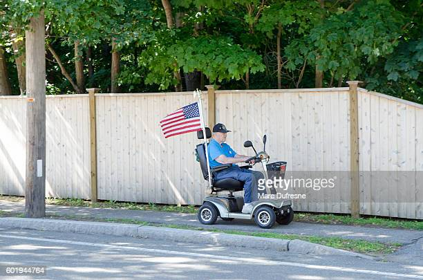 Proud elderly american in a four-wheeled electrical mobility scooter