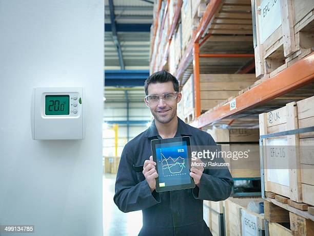 Proud factory worker showing energy saving on digital tablet in factory, portrait