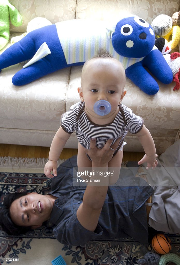 Proud father holding up son. : Stock Photo