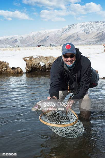 Proud Fisherman Holding Up His Rainbow Trout In Winter