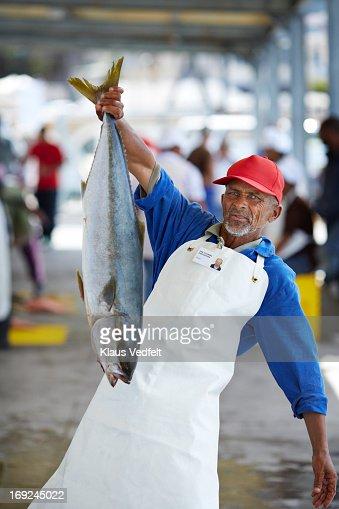 Proud fishworker holding fish