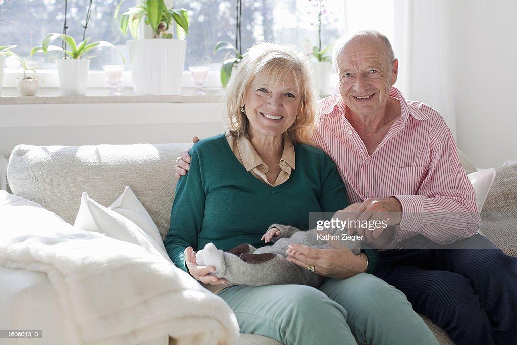 proud grandparents holding newborn grandson : Stock Photo