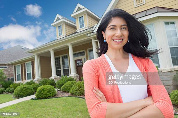 Proud Hispanic woman standing in front of newly purchased home