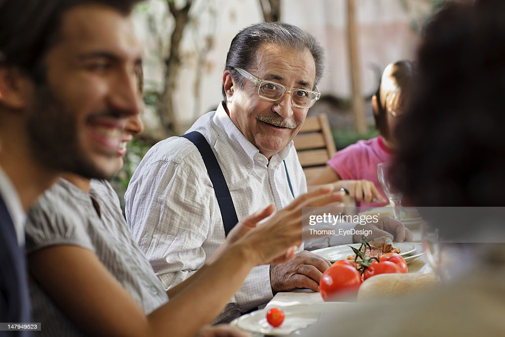 Proud Italian Grandfather having lunch with family