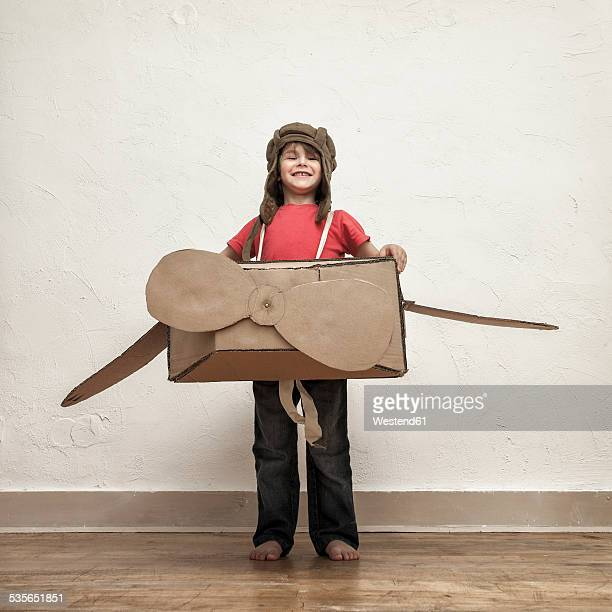 Proud little boy playing with pilot hat and cardboard box aeroplane