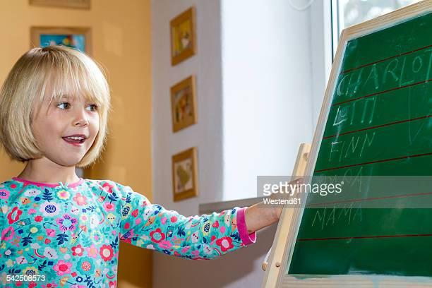 Proud little girl looking at blackboard
