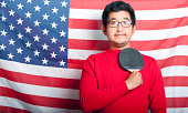 Proud  Man holding table tennis paddle against US Flag