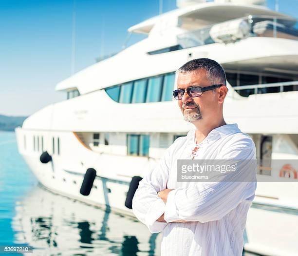 Stolzer Mann vor seinem yacht