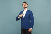 Proud man pointing finger himself. portrait of handsome bearded businessman in blue suit and white shirt, with smart watch. Indoor studio shot, isolated on light blue background