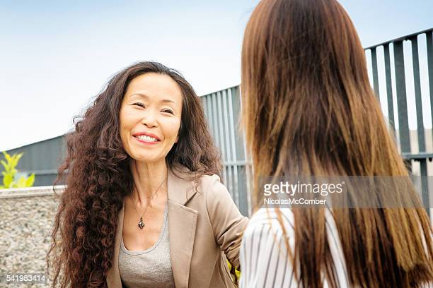 Proud mature female Japanese  mentor smiles at her protegee