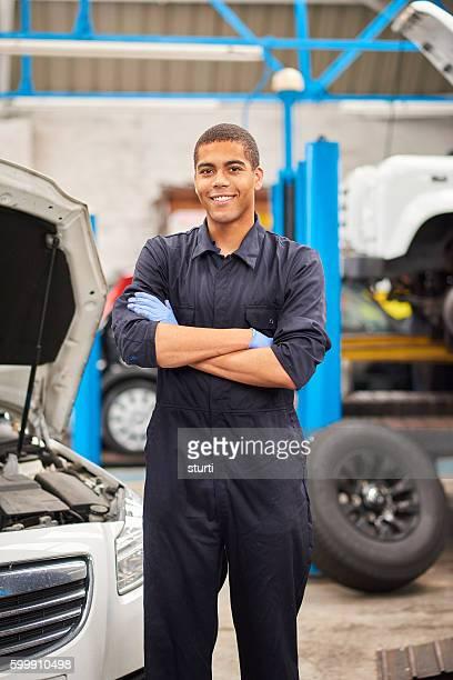 Proud mechanic smiles to camera