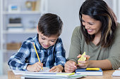 Beautiful mid adult Asian mom smiles proudly at his son while he does his math homework. He is writing in a notebook. The mom is holding math flashcards.