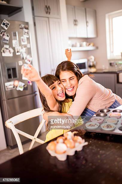 Proud mom hugging her little girl in the kitchen