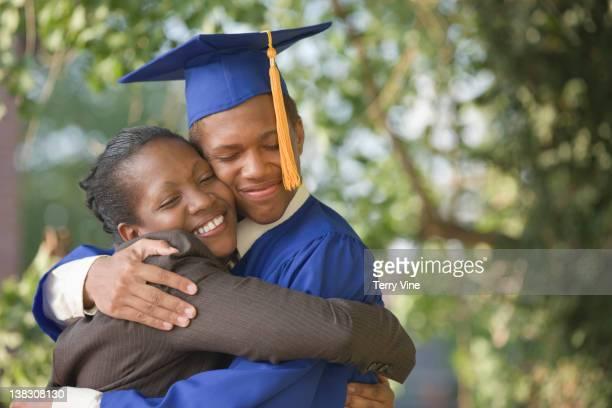 Proud mother hugging graduating son