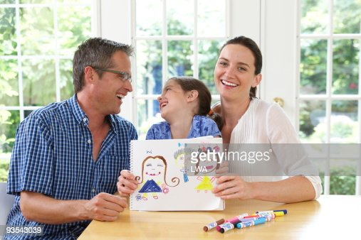 Proud parents with daughter and her drawing : Stock Photo