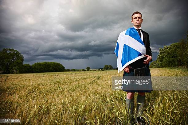 Proud scotsman in cornfield with kilt and saltire