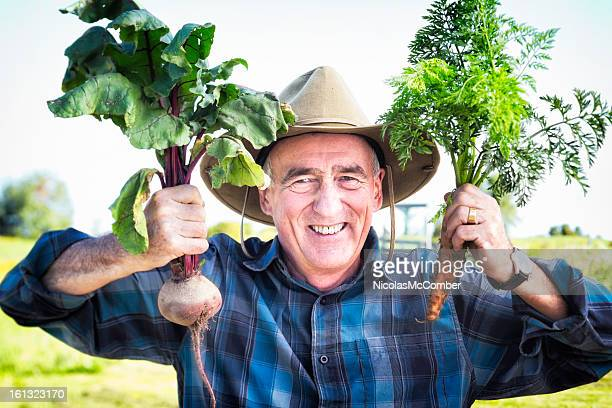 Proud senior farmer shows off his root vegetables