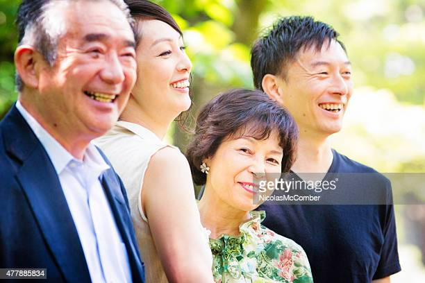 Proud senior Japanese woman with her family in park