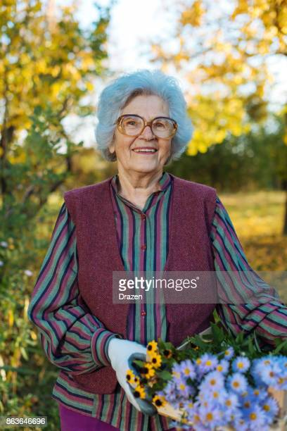 Proud senior woman holding crate with flowers in garden