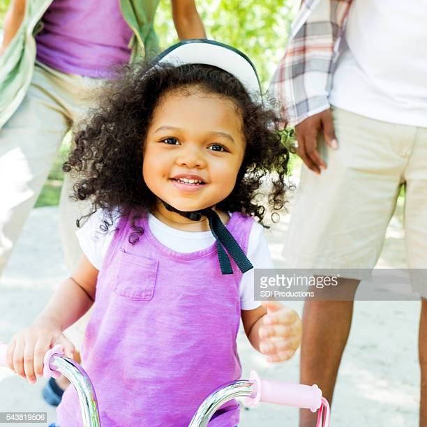 Proud toddler riding tricycle in the park