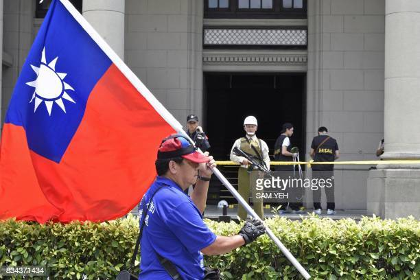 A prounification activist displays a Republic of China flag near the ropedoff rear entrance to the Presidential Palace complex where a samurai...
