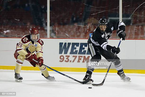 Providence College Friars defenseman Vincent Desharnais passes the puck away from Boston College Eagles forward Julius Mattila during a Frozen Fenway...