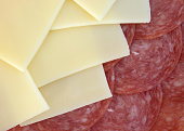 A close view of slices of provolone cheese and genoa salami illuminated with natural light.