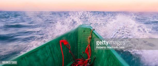 Prow of fishermen boat braving the sea swell as they return to the shore in the afternoon Concept image for adversity risk and resilience