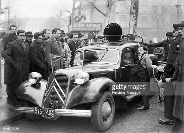 Près de la Place de la Madeleine un groupe de personnes écoute attentivement les dernières nouvelles diffusées par hautparleurs à Paris France circa...