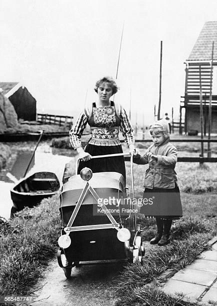 Près d'une rivière une femme en tenue traditionnelle et accompagnée d'une petite fille derrière une poussette équipée d'un triangle réfléchissant et...