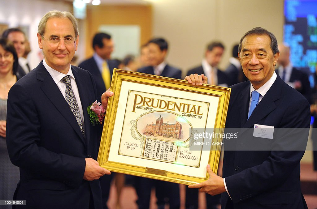 Prudential chairman Harvey McGrath (L) and Ronald Arculli, chairman of ther Hong Kong Exchange (HKEX) hold a picture as they attend Prudential's listing ceremony in Hong Kong on May 25, 2010. McGrath defended a planned takeover of Asian insurer AIA as the British company's shares started trading in Hong Kong and Singapore to help fund the mega-deal. Prudential, which is keeping its primary listing in London, is hoping to woo Asian investors ahead of its planned 21-billion-USD rights issue to buy the Asian arm of troubled US insurer American International Group (AIG).