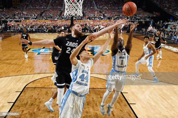 Przemek Karnowski of the Gonzaga Bulldogs goes for a rebound against Justin Jackson and Theo Pinson of the North Carolina Tar Heels in the first half...