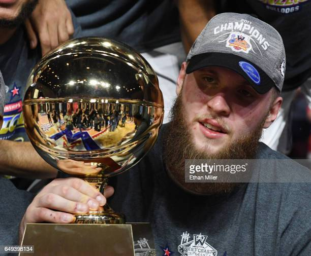Przemek Karnowski of the Gonzaga Bulldogs holds the trophy following the team's 7456 victory over the Saint Mary's Gaels to win the championship game...