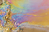 Abstract of bright vibrant oil spill shapes of pollution on the surface of water. Patterns of multi-coloured pollutants releasing hazardous chemicals into the environment.