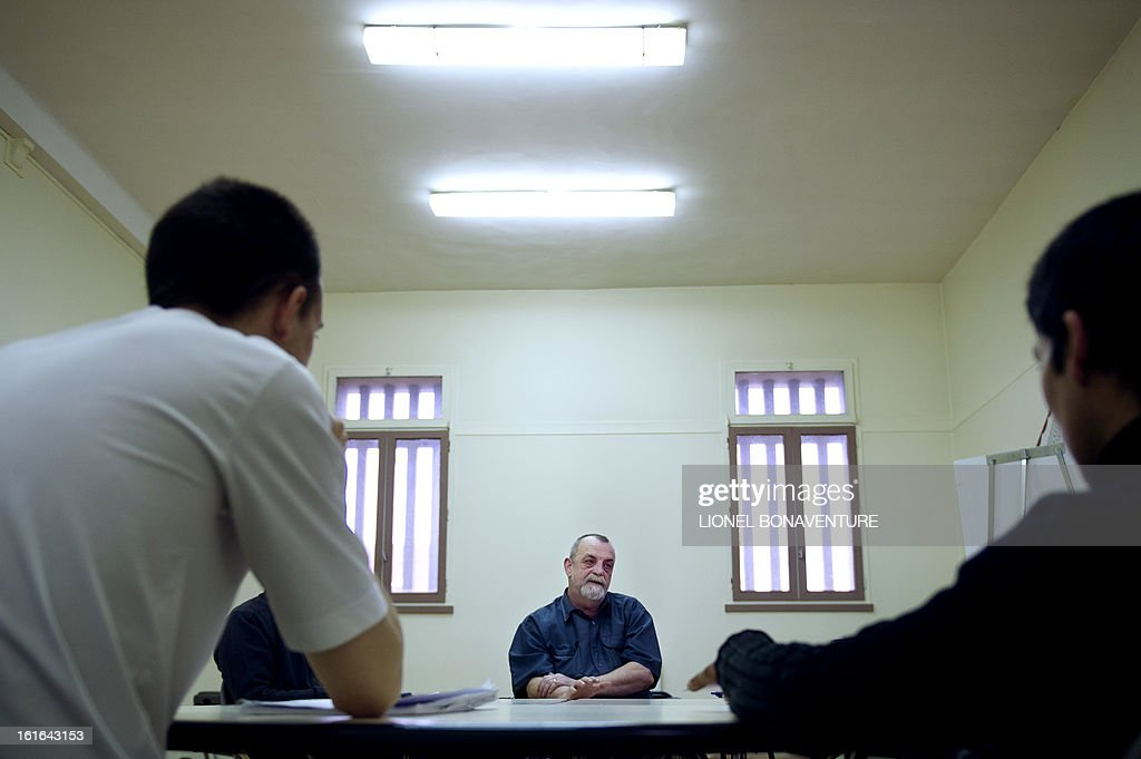 Psychiatric nurse (top) leads a work group of sex offenders in the hospital section of the Frenses detention centre in Fresnes on February 7, 2013. This pilot program, inspired from similar projects in Canada, aims to stop sex offenders from repeating offences. AFP PHOTO / LIONEL BONAVENTURE