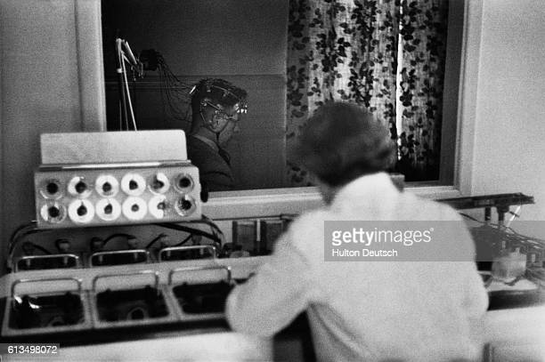 A psychiatric patient is connected via electrodes to an electroencephalograph machine which generates an image of the brain's electrical activity The...