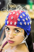 Picture of a latin girl with electrodes in her face, chest and head to record psychophysiological signals for research purposes. Electrocardiogram (ECG), electroencephalogram (EEG) and electrooculogra