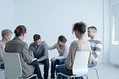 Psychotherapist comforting man with depression during psychotherapy meeting