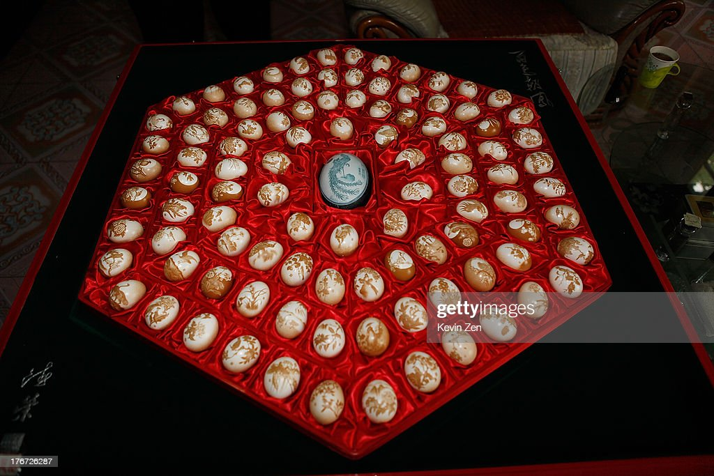 Pu Derong shows one of his works on eggshell, which consists of 108 different birds on each eggshell, on July 1, 2013 in Zhuozhou, Hebei Provience, China.Egg carving, an art form originated in the Ming and Qing Dynasties has grown in popularity recently. Pu Derong, from Zhuozhou City, Hebei Province has carved eggs since 1995, and after becoming recognised for his work he now works for museums to carve for them.