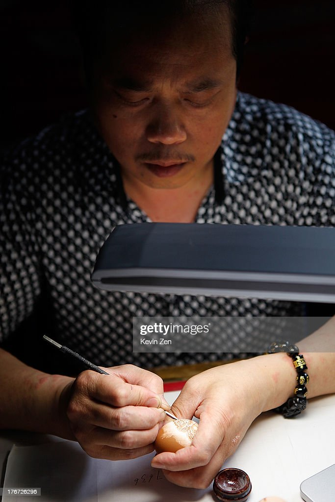 Pu Derong works on eggshell at home on July 1, 2013 in Zhuozhou, Hebei Provience, China. Egg carving, an art form originated in the Ming and Qing Dynasties has grown in popularity recently. Pu Derong, from Zhuozhou City, Hebei Province has carved eggs since 1995, and after becoming recognised for his work he now works for museums to carve for them.