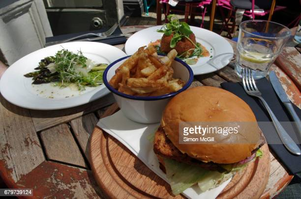 Pub lunch of a chicken burger, potato chips, arancini ball and asparagus on a pub outdoor terrace
