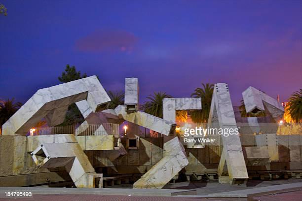 Public artwork on city plaza at dusk