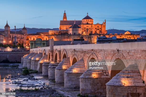 Public Bridge On The River At Dusk With Mosque In The Background In Cordoba Andalusia Spain