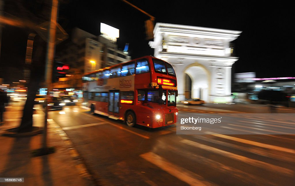 A public bus drives past a replica of the Arc de Triomphe stands illuminated at night in central Skopje, Macedonia, on Saturday, March 16, 2013. Macedonia's economy contracted by a real 0.3% on the year in 2012, compared to a growth of 2.8% a year earlier, an estimate released by the country's statistics office showed. Photographer: Oliver Bunic/Bloomberg via Getty Images
